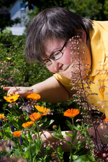 disabled woman cuts flowers in the garden